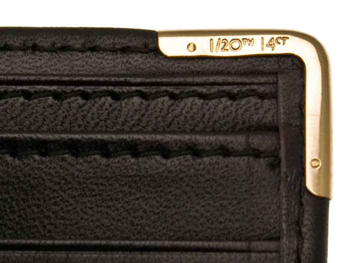 Detail of a hand-riveted 14ct rolled gold corner on a leather wallet